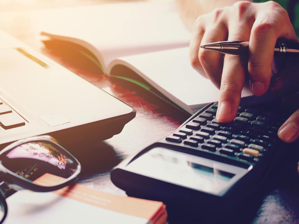 Jemand kalkuliert ERP System Kosten auf einem Taschenrechner